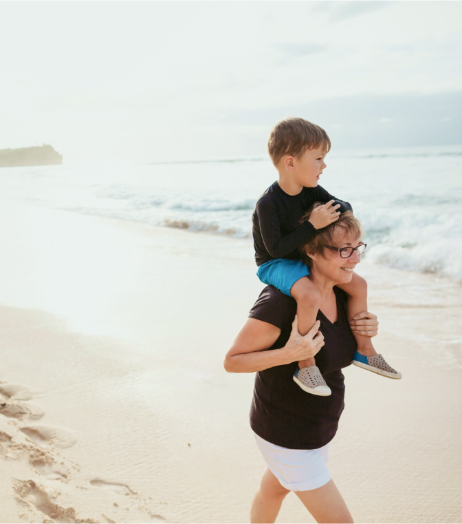Grandmother and grandson walking on a beach