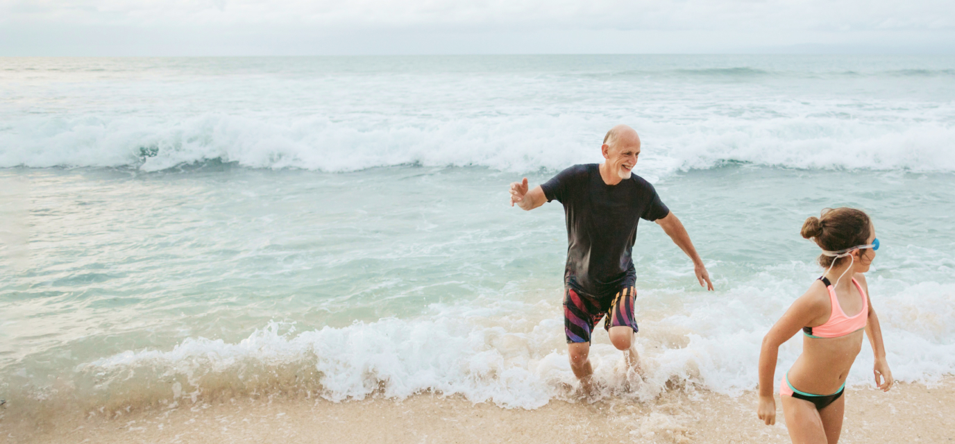 Grandfather and grandchild running on a beach