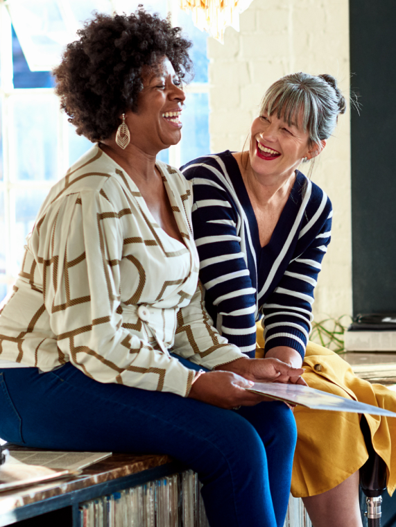 Two women sitting on a countertop top laughing together