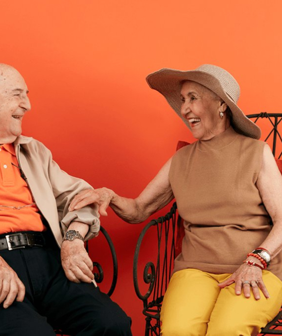 Couple sitting in chairs laughing against an orange background