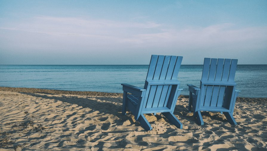 two blue beach chairs on the sand looking out at the water