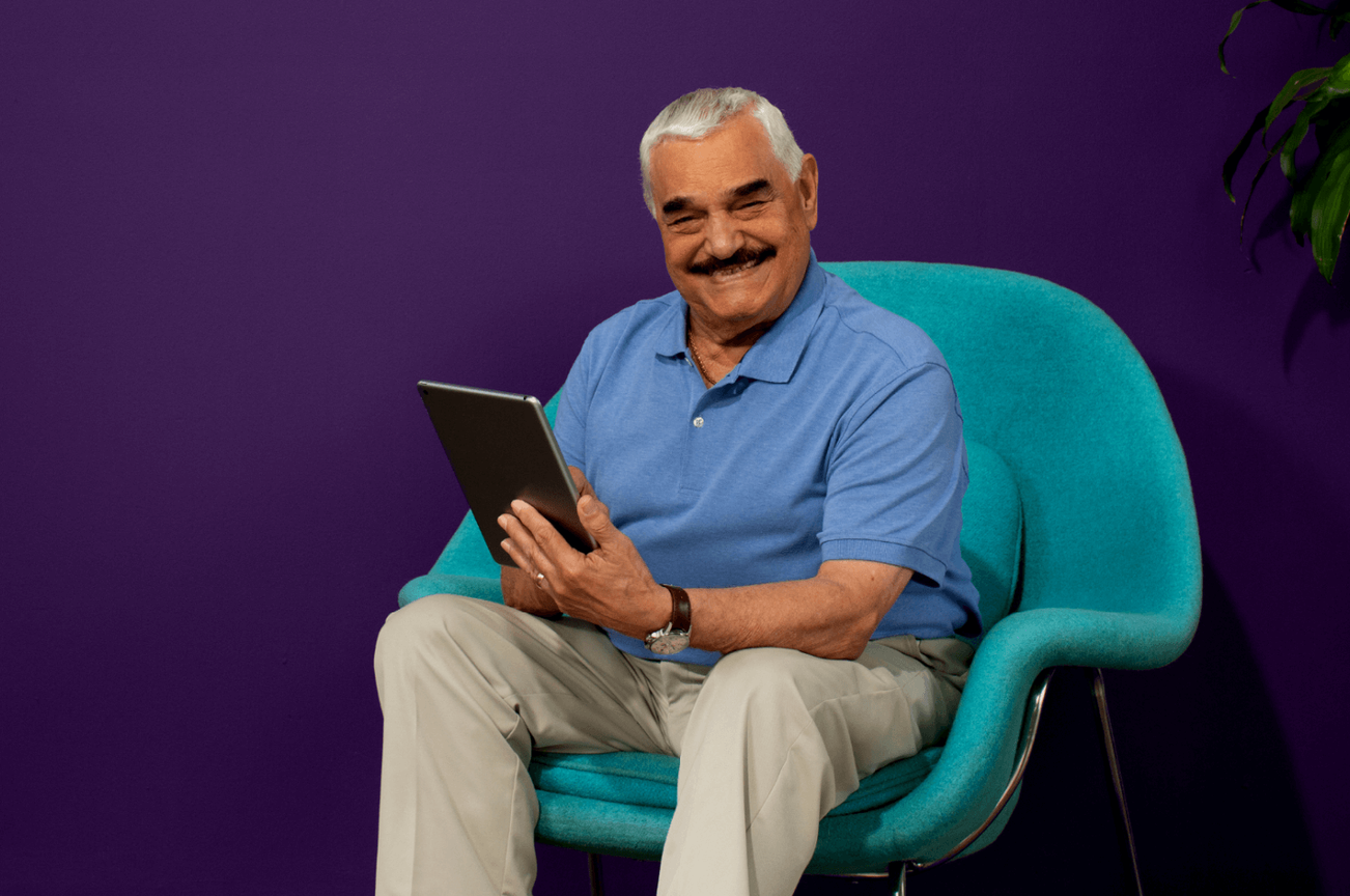 Clover Health member holding a tablet and smiling while wearing a blue shirt and khaki pants sitting in a blue chair against a purple background.