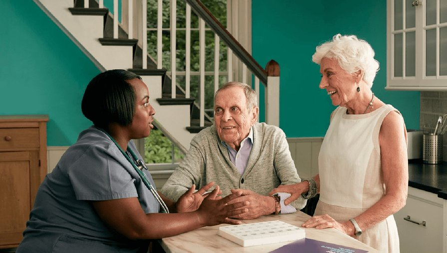 Clover Health nurse sitting at the kitchen table discussing plan benefits with two Clover members.