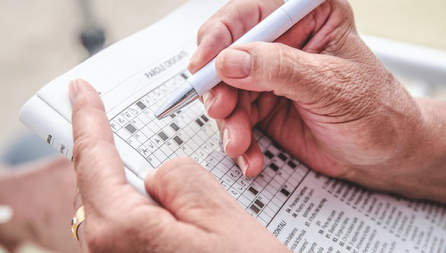 a close-up of a woman's hands holding a magazine and using a purple pen to do a crossword puzzle