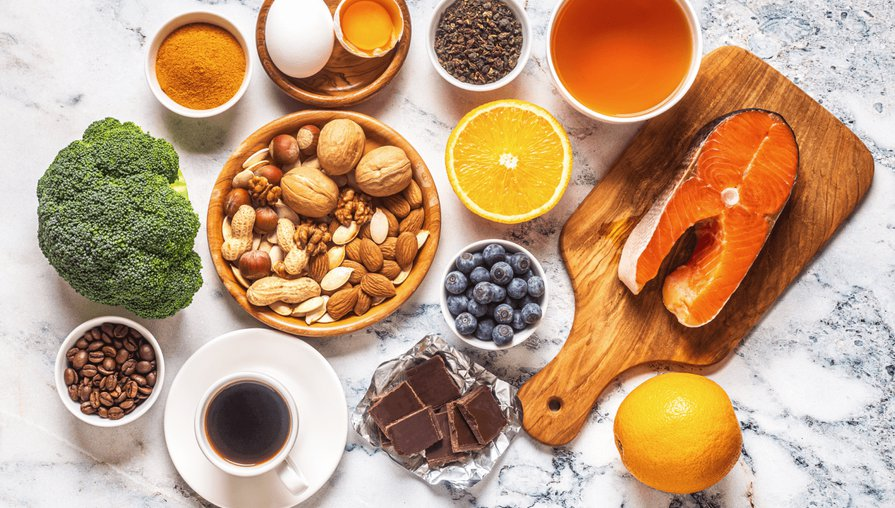 bowls of healthy food on a marble countertop, including broccoli, mixed nuts, salmon, citrus fruits, an egg, coffee, blueberries, and chocolate
