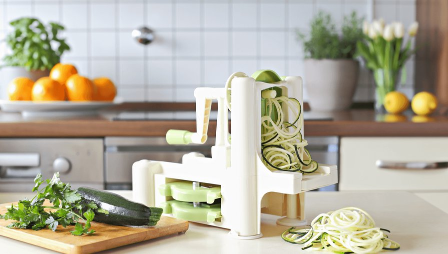 a kitchen with a spiralizer on the counter cutting zucchini spirals next to a cutting board with half a zucchini