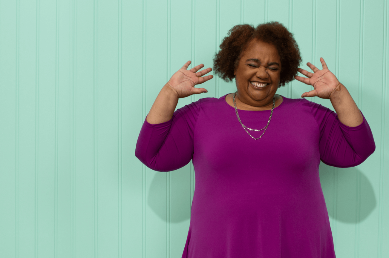 Clover Health member throwing up her hands with an overwhelmed expression wearing a purple shirt standing against a seafoam green background