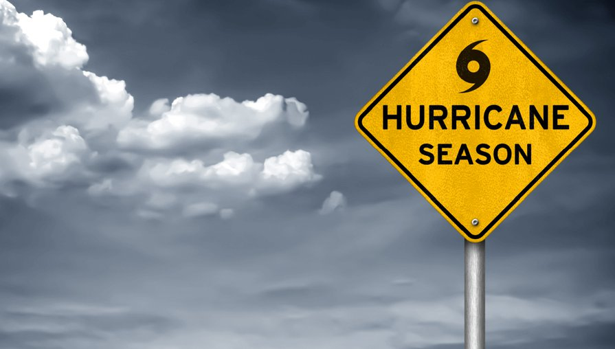 yellow street sign that says hurricane season in front of a dark, cloudy sky