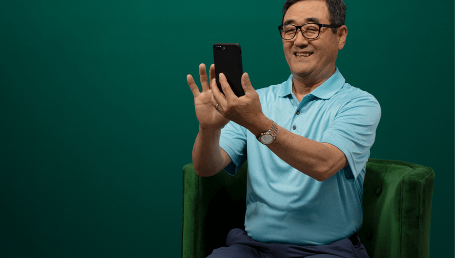 Clover Health member looking at his smartphone, he is wearing a blue polo shirt and sitting in a green chair against a darker green background