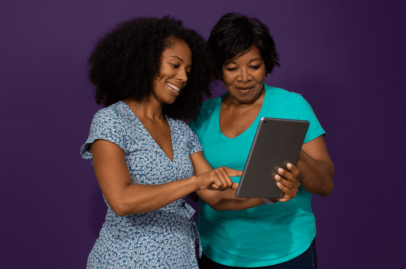 Clover Health member wearing a teal T-shirt standing next to her daughter in a blue dress looking at a tablet together