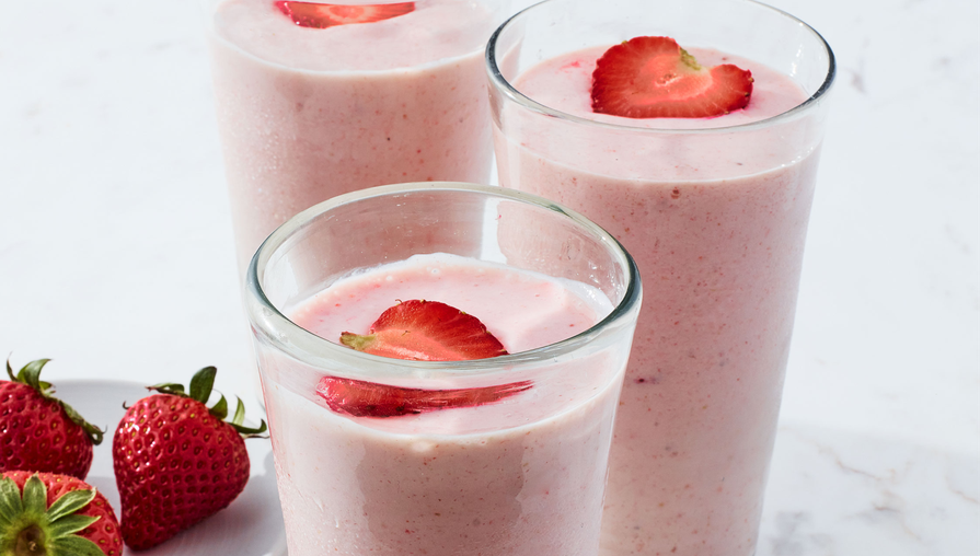 three strawberry smoothies in glasses on a marble countertop alongside a plate of strawberries