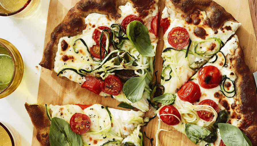 pizza with tomatoes, zucchini spirals and basil on a cutting board
