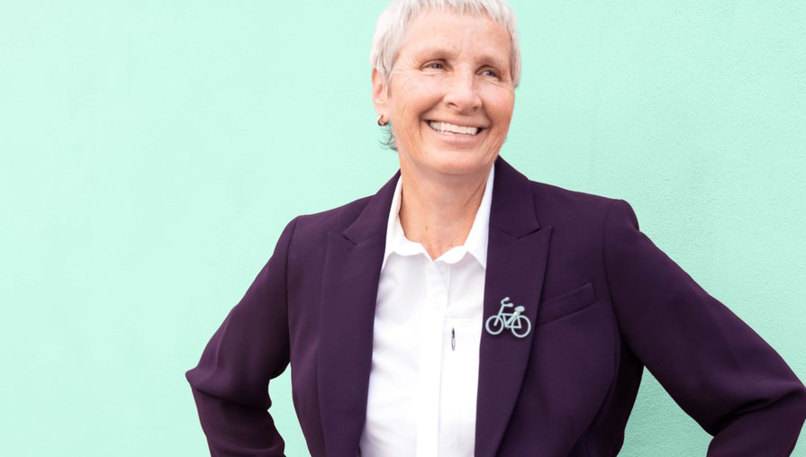 Clover Health member Paula wearing a purple blazer and white button up shirt standing against a mint green background