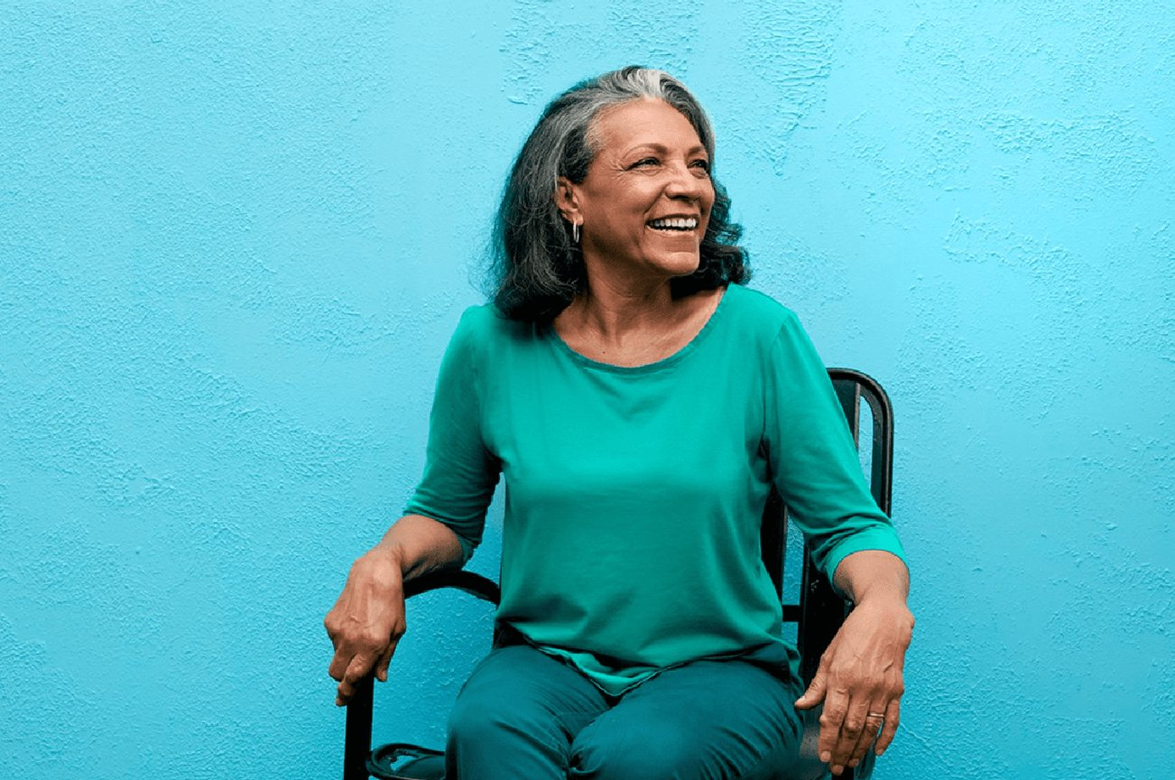 Clover Health member wearing a green shirt sitting in a chair against a blue background