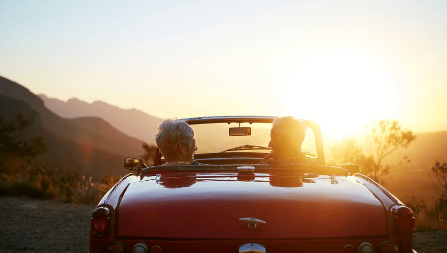 senior couple sitting in a red convertible at a lookout point in the mountains at sunset