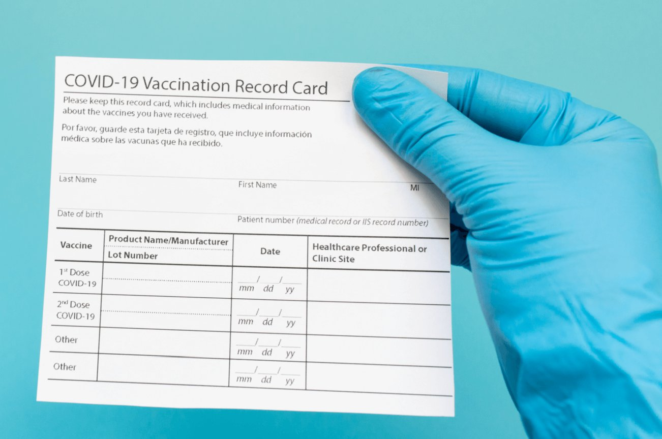 hand with a blue medical glove holding a COVID-19 vaccination record card up against a blue background
