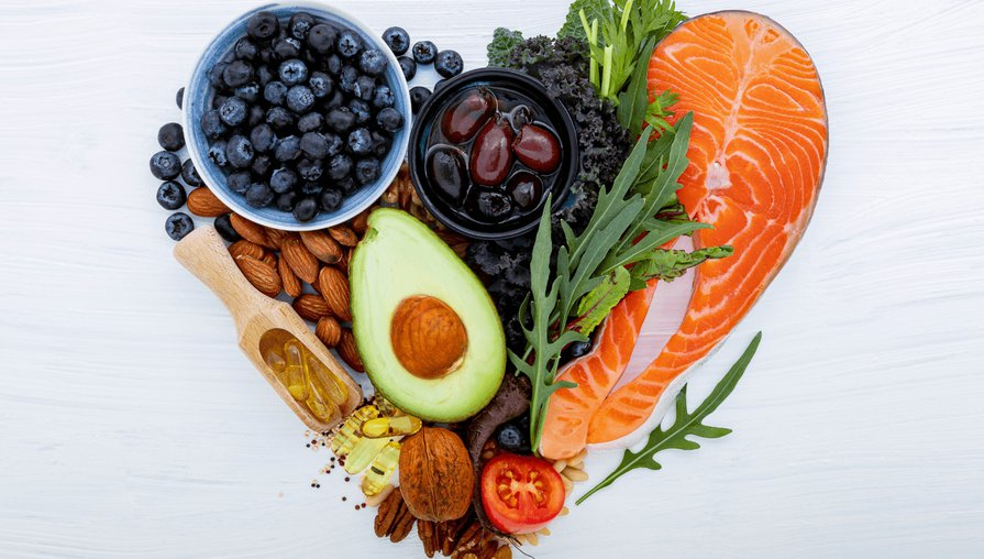 heart made out of different heart-healthy foods, including blueberries, salmon, avocado, and leafy greens