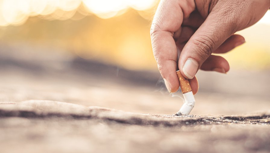hand holding a cigarette and putting it out on the pavement