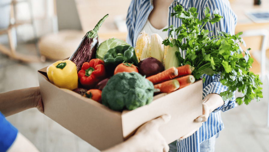 person hand delivering a box of vegetables to a customer's home