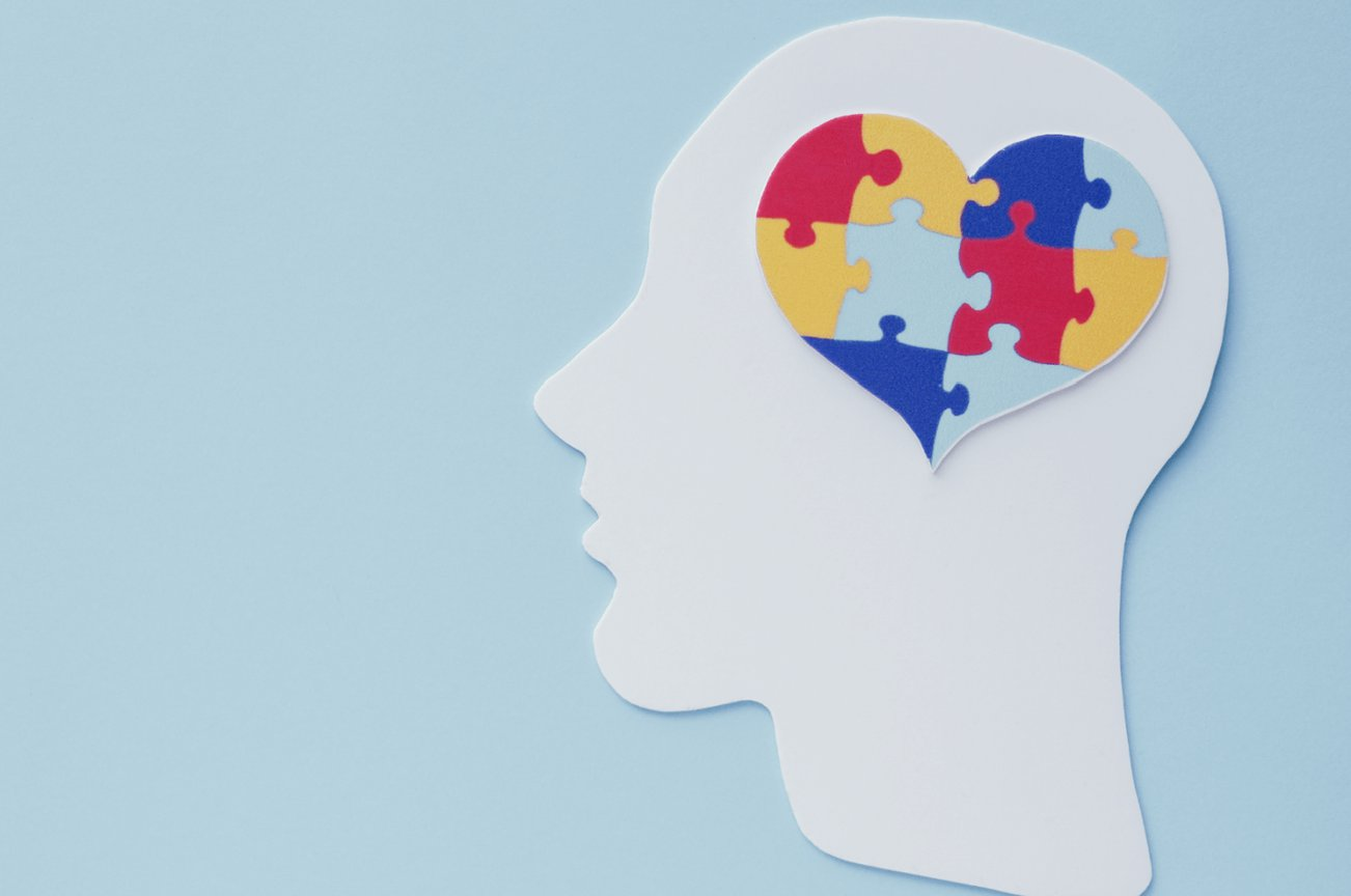 blue background with a white paper cutout of a person's head with colorful puzzle pieces near the brain that come together to form a heart