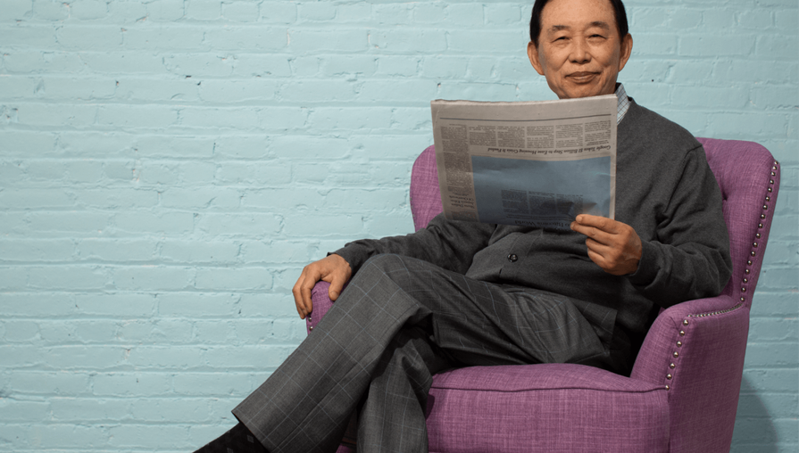 Clover Health member reading a newspaper while sitting in a purple chair against a blue background